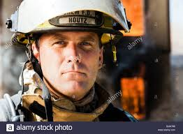 portrait of a firefighter with fire in background stock photo