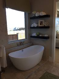 stand alone tub with open shelves and i adore the tile on the