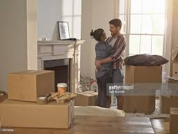 a young professional couple hugging in new home stock photo