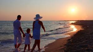 family walking away from on in sunset stock