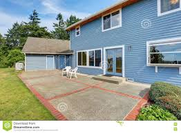 blue house backyard with concrete floor patio area and well kept
