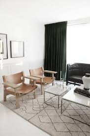 monochrome living room with spanish chairs in tan leather and dark