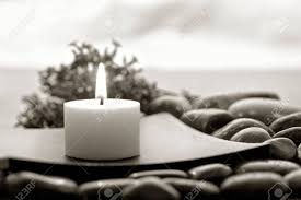 zen inspired aromatherapy candle burning on a plate with stones