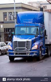 bright modern big rig blue day cab semi truck with roof spoiler