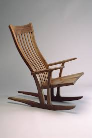 comfortable walnut wood rocking chair with flexible back slats hand carved and ed by seth rolland