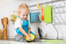 cuisine garcon mignon enfant garçon de 2 ans vaisselle dans la cuisine banque d
