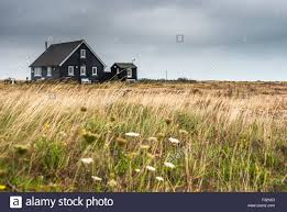 an isolated small wooden house on the wind swept beach of