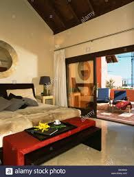 Spanish Bedroom Furniture by Red Stool Below Bed With Faux Fur Throws In Modern Spanish Bedroom