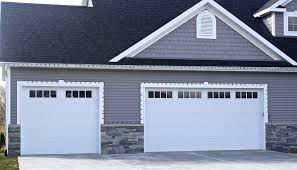 white arriage style garage door with mission window inserts in