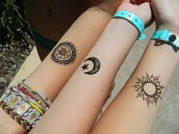 peace symbol and tree henna on left forearm