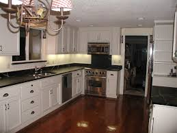 travertine countertops white kitchen cabinets with black lighting