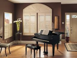 decorating charming white sunburst shutters on brown wall matched