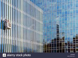 two men washing outside of glass walls of huge office building