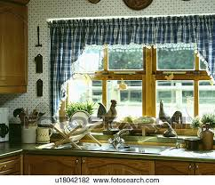 stock photo of blue white checked curtains above chicken ornaments