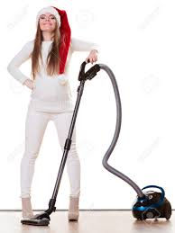 woman vacuuming the house funny in santa helper hat with