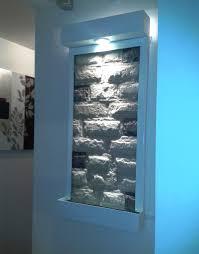 fuente de pared blanca con piedra de marmol blanco con unos