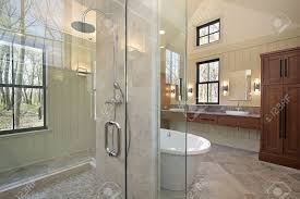 master bath in luxury home with glass shower in middle of room