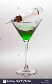 martini green loaded hypodermic syringe on top of martini glass with green