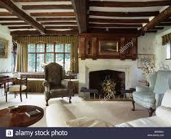 dark green wing chair in front of window beside fireplace in