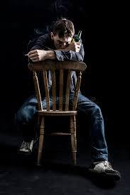 depressed man on chair smoking cigarette royalty free stock photos