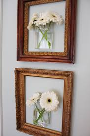 hang mounted vases with real flowers inside empty picture frames