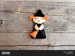 halloween cute felt witch with broom on old wooden background