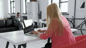 young business woman working at shared desk in trendy hipster