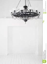 vintage black chandelier with candles in an empty room stock