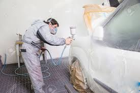car body painter spraying paint or color on bodywork in a garage