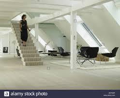 Open Plan Apartment by Woman Walking Down Staircase Into Open Plan Copenhagen Loft Stock
