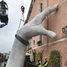 support monumental hands rise from the water in venice to