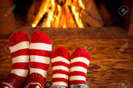 mother and children feet in christmas socks near fireplace people