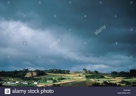 sun breaks through a sky in the countryside before town of