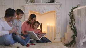 family read book sitting on sofa in front of fireplace in