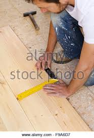 measuring a wooden plank with a measure with diy