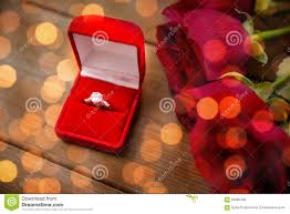 close up of diamond engagement ring and red roses stock photo