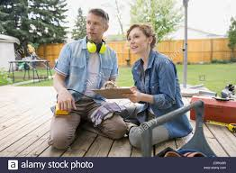 couple with clipboard preparing to sand backyard deck stock photo