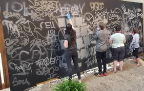 the city of calgary street art program for youth group of youth spray painting words on mural