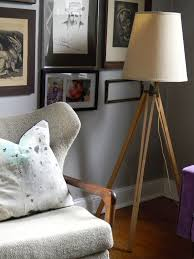 brown wooden tripod floor lamp with cream shade on brown wooden