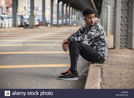 a portrait of a young man in gym clothes sitting on the curb shot