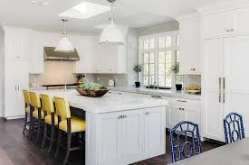 white and gray kitchen with yellow leather bar stools