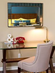 modern glass desk in a bedroom with wooden legs and an upholstered