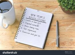 top of coffee cup new years resolutions written on notepad stock photo 737035591