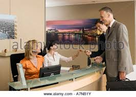 Two Person Reception Desk Two Receptionists Working At Reception Desk Woman Holding Phone