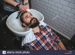 pretty verry young boys washing hairs hairdresser washing hair of young attractive man with beard in