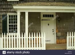 colonial american house with white picket fence and strap hinges