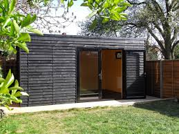garden room in crouch end with gym and storage black shed black