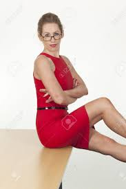 provocative secretary wearing a red dress and posing sitting