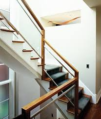 walnut wood railing matte aluminum edging on the glass creates a