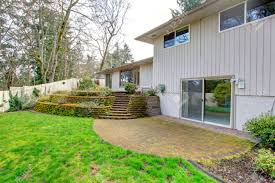 green backyard with beautiful terrace deck and brick floor walkout
